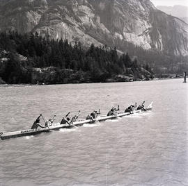 Young men paddling large canoe