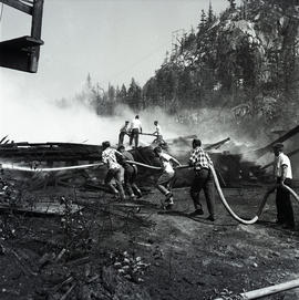 Men putting out fire with hose