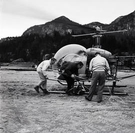 Men doing something to helicopter