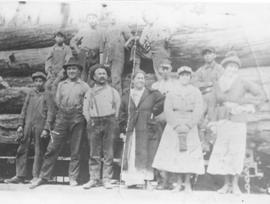 Group of people in front of load of logs