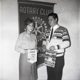 People with Rotary Club sign