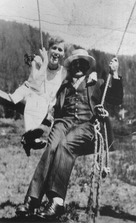 Unidentified man and woman on swing