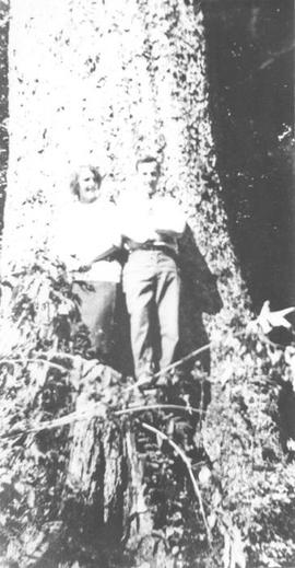 Man and woman posing before a tree