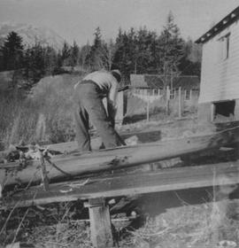 Moses Billy working on a dugout canoe